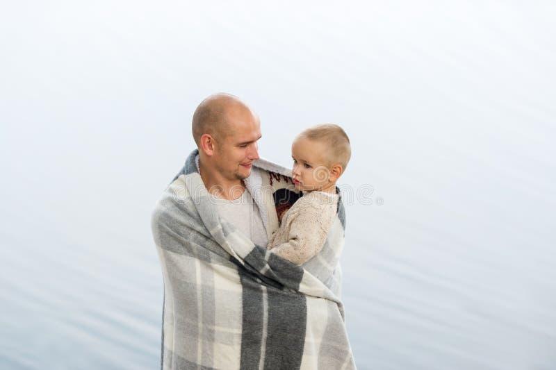 Den unga fadern rymmer den lilla sonen på händer royaltyfri bild