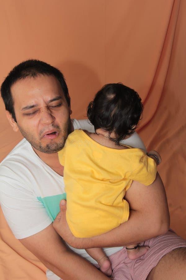 Den unga fadern som tar omsorg av, behandla som ett barn dottern som rymmer i armar fotografering för bildbyråer