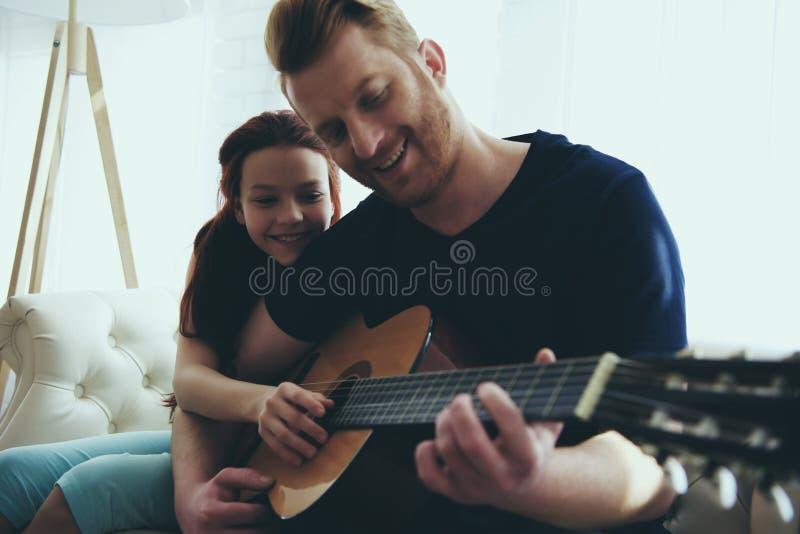 Den unga fadern undervisar den lilla dottern att spela arkivfoto