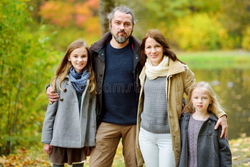 Den unga familjen av fyra som har gyckel i höst, parkerar Föräldrar och två ungar som tycker sig om på varm nedgångdag i stad, pa royaltyfria bilder