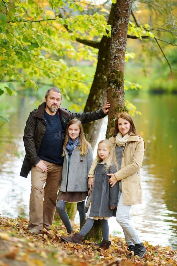 Den unga familjen av fyra som har gyckel i höst, parkerar Föräldrar och två ungar som tycker sig om på varm nedgångdag i stad, pa royaltyfri bild