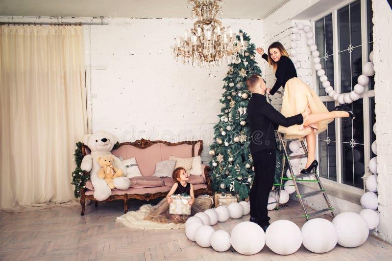 Den unga familjen dekorerar upp julgranen, hållande gåva för rödhårig flicka, medan sitta på golv royaltyfri foto