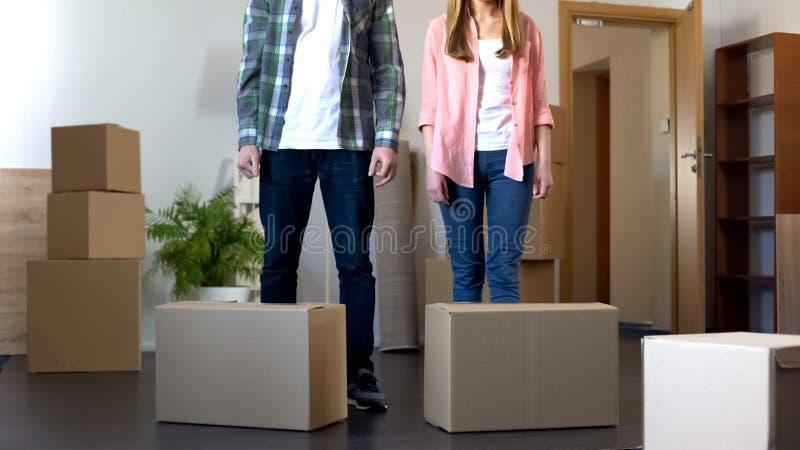 Den unga familjen flyttar sig till den nya lägenheten, packad upp saker omkring i kartonger arkivbild