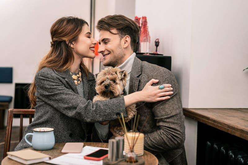 Den unga familjen kramar, medan besöka ett kafé med deras husdjur royaltyfri fotografi