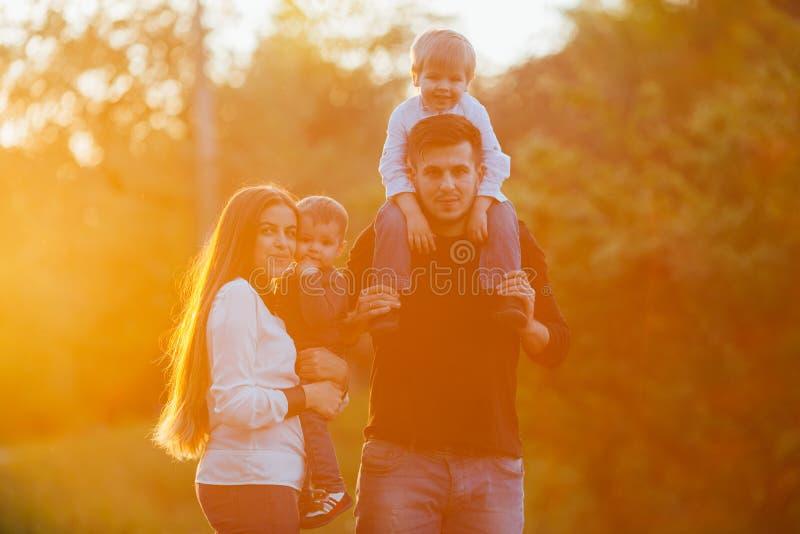 Den unga familjen med barn som in går, parkerar Fader, moder och två söner fotografering för bildbyråer