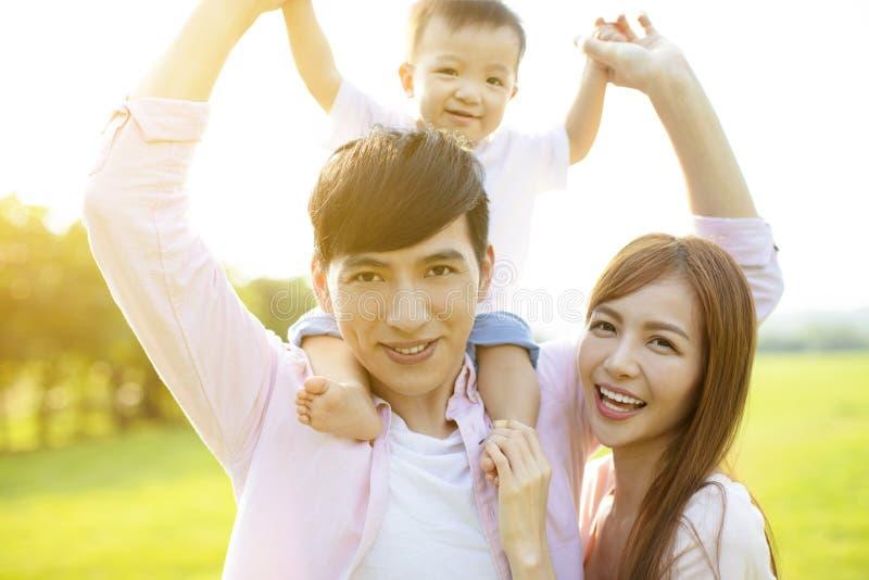 Den unga familjen med behandla som ett barn ha gyckel i natur royaltyfri foto