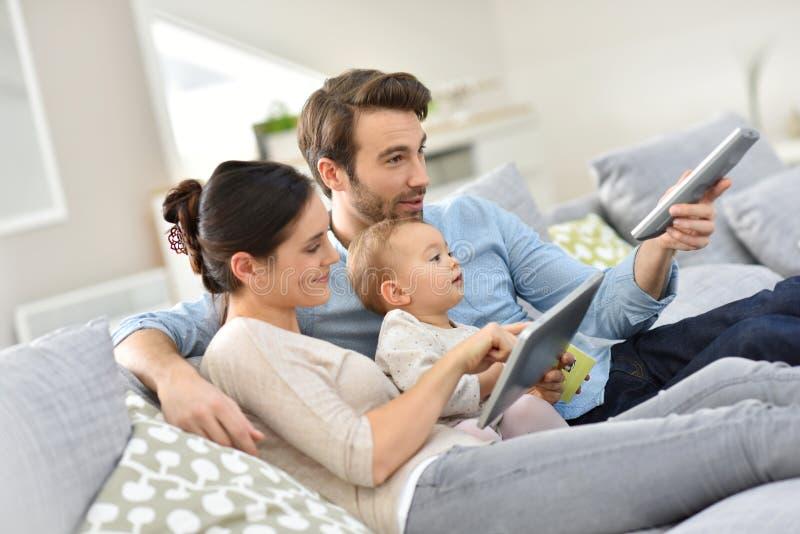 Den unga familjen med behandla som ett barn hemmastadd utgiftergodatid arkivbilder