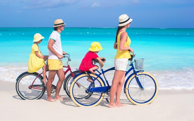 Den unga familjen med små ungar rider på cyklar arkivfoton