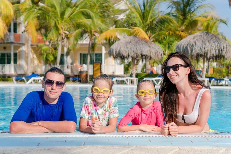 Den unga familjen med två ungar tycker om sommarsemester i utomhus- pöl royaltyfri fotografi
