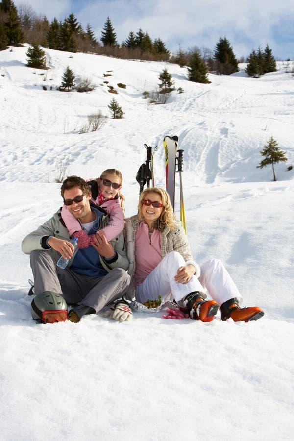 Den unga familjen skidar på semester royaltyfria bilder