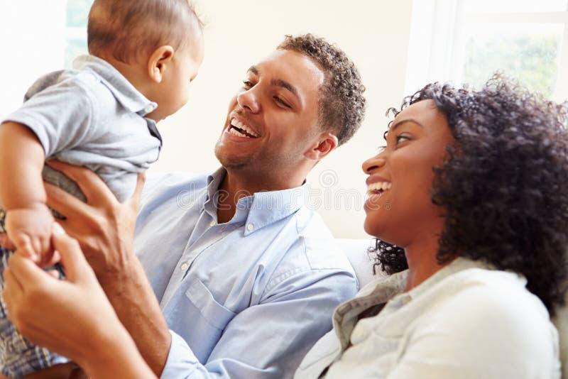 Den unga familjen som spelar med lyckligt, behandla som ett barn sonen hemma royaltyfri bild