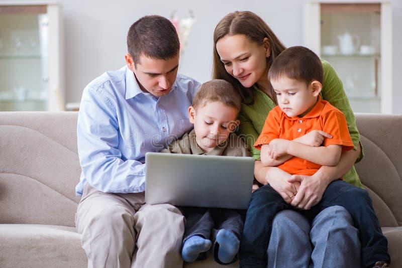 Den unga familjen som surfar internet och ser foto arkivbild
