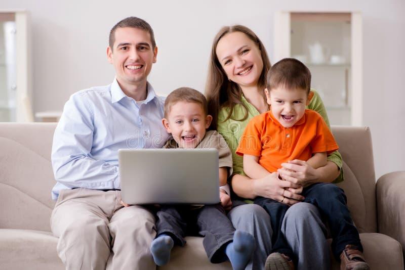 Den unga familjen som surfar internet och ser foto arkivfoton