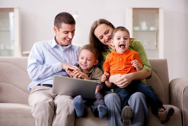 Den unga familjen som surfar internet och ser foto royaltyfria bilder