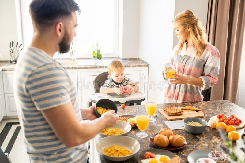Den unga familjen som tycker om frukosten med, behandla som ett barn royaltyfria foton
