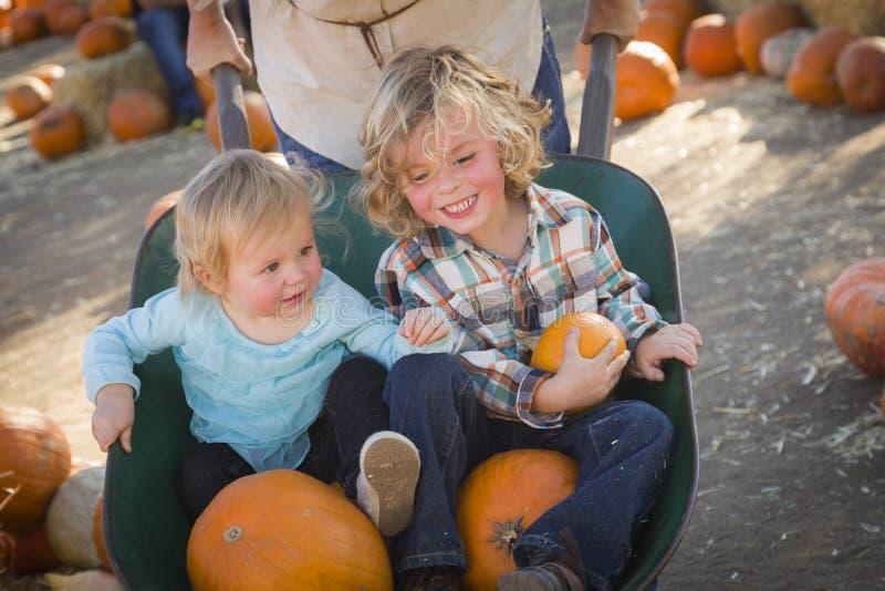 Den unga familjen tycker om en dag på pumpalappen fotografering för bildbyråer