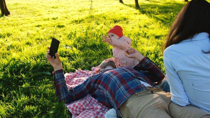 Den unga familjen vilar på naturen, frågar ett småbarn för en smartphone, fadertagandeen bort telefonen från behandla som ett bar royaltyfria bilder