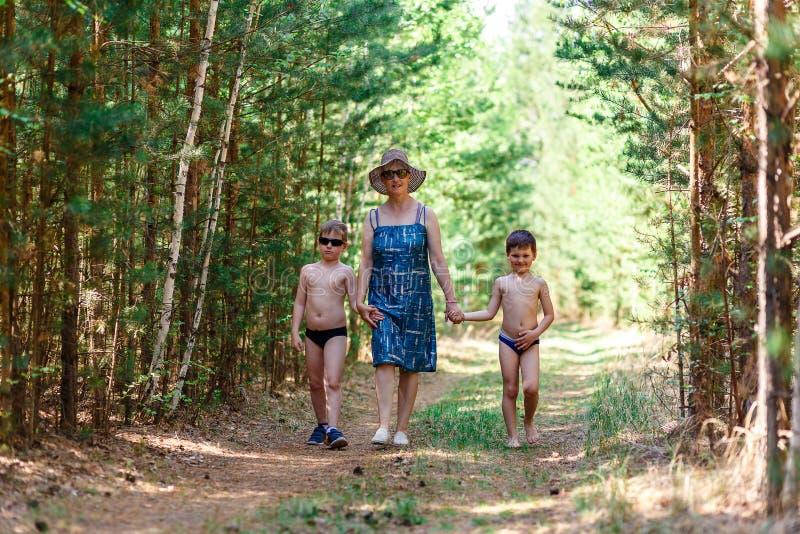 Den unga farmodern går i träna med två barnbarn royaltyfri fotografi