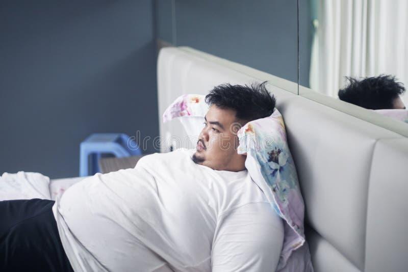 Den unga feta mannen ser eftertänksam på sängen fotografering för bildbyråer