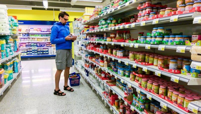 Den unga finlandssvenska mannen som väljer, behandla som ett barn mat i en suomisupermarketS-marknad, i Tammerfors royaltyfri foto