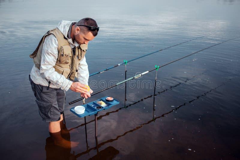 Den unga fiskaren står i vatten barfota Han lutar till den öppnade plast- asken med konstgjorda beten där två arkivbilder