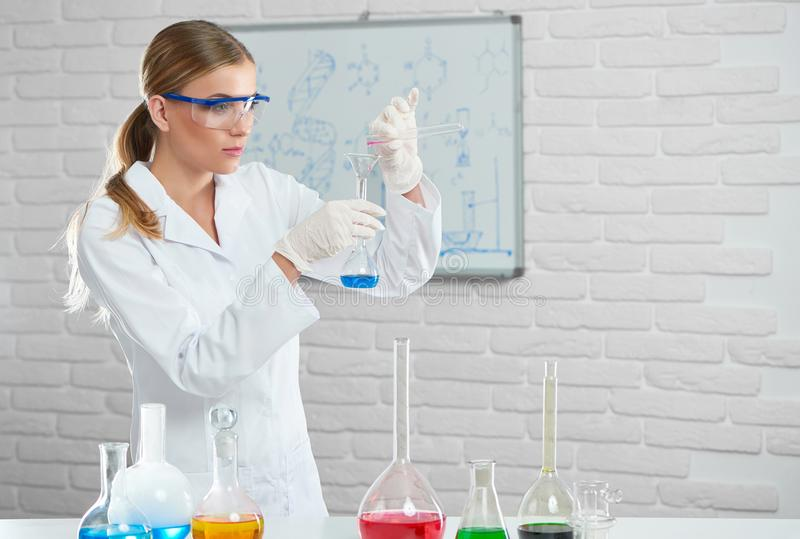 Den unga forskaren arbetar med kemiska flytande royaltyfri foto