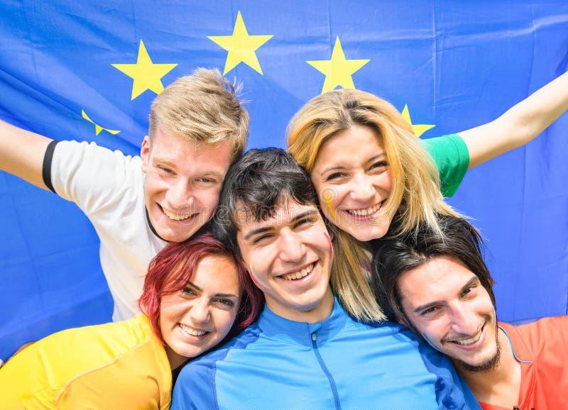 Den unga fotbollsupportern fläktar bifall med den europeiska flaggan arkivbild