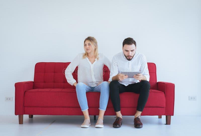 Den unga frun grälar med makekonflikt och borrapar i vardagsrummet, negativ sinnesrörelse royaltyfri bild