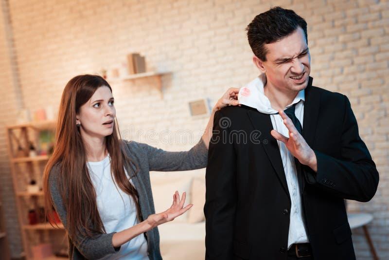 Den unga frun grundar avtrycken av kyssen på hennes krage för skjortan för make` s dricka för alkohol royaltyfri foto