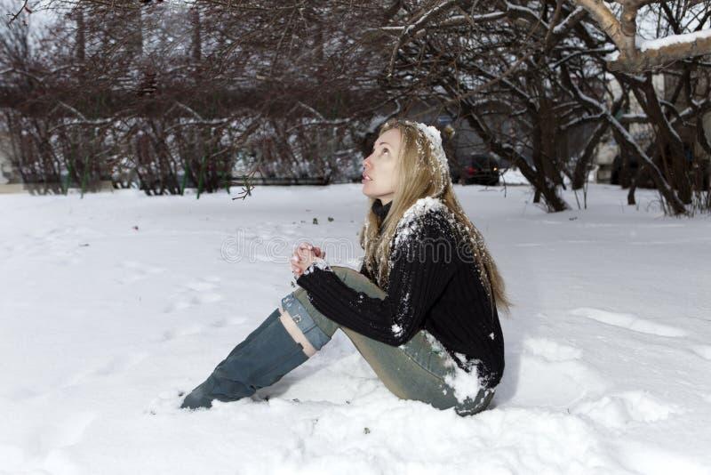 Den unga fryste kvinnan under den fallande snön arkivfoton