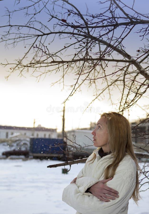 Den unga fryste kvinnaställningen under den fallande snön arkivfoton