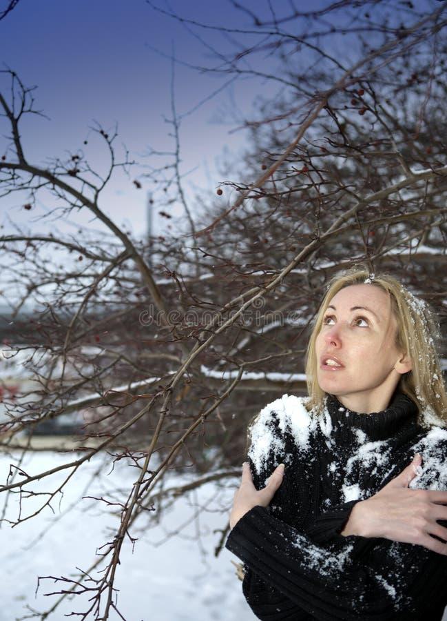 Den unga fryste kvinnaställningen under den fallande snön under ett träd royaltyfri fotografi