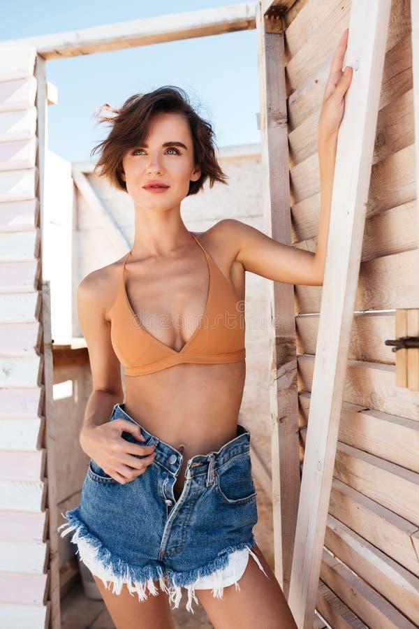 Den unga fundersamma damen i bikini och grov bomullstvill kortsluter anseende i omklädningsrum med låsbara skåp som dreamily åt s arkivfoton