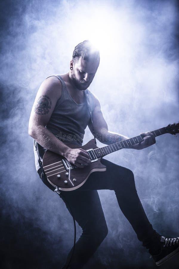 Den unga gitarrspelaren vaggar in konsert royaltyfri bild