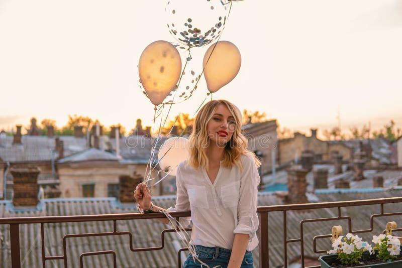 Den unga gladlynta flickan rymmer många ballonger på balkong eller taket royaltyfria foton