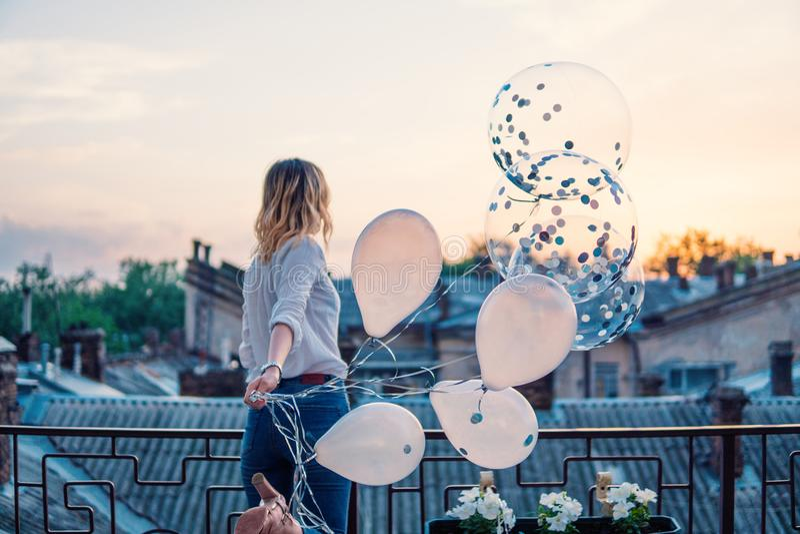 Den unga gladlynta flickan rymmer många ballonger på balkong eller taket arkivbild