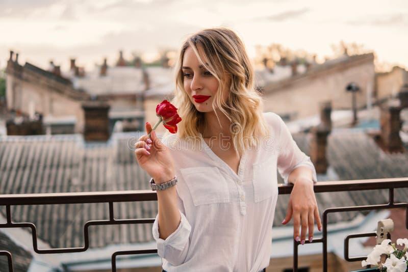 Den unga gladlynta flickan rymmer den röda blomman på balkong eller taket arkivbilder