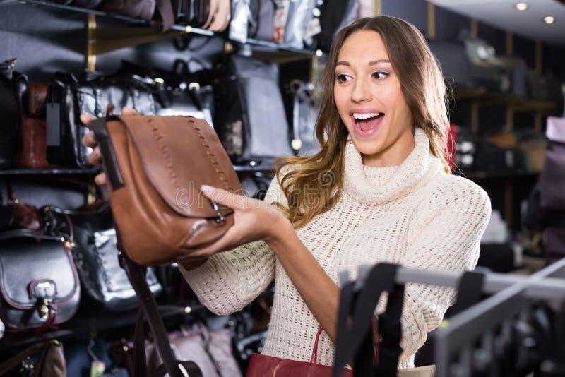 Den unga gladlynta handväskan för kvinnaköpandeläder shoppar in fotografering för bildbyråer