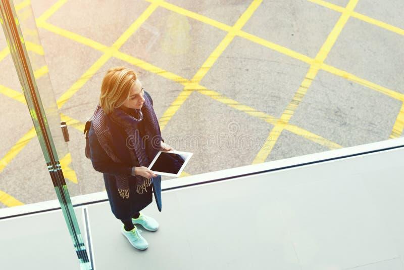 Den unga gladlynta kvinnan med den digitala minnestavlan i händer ler för någon royaltyfri fotografi
