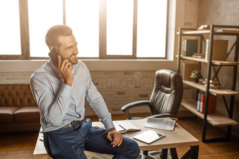 Den unga gladlynta stiliga affärsmannen sitter på tabellen och samtal på telefonen i hans eget kontor Han ler Affärssamtal säkert royaltyfri fotografi