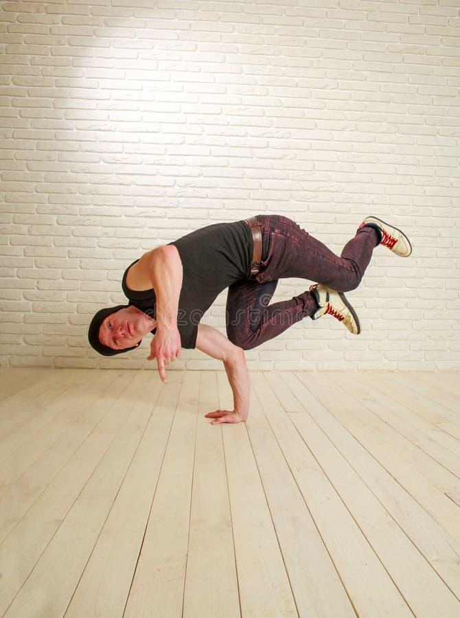 Den unga grabben i h?ft-flygtur f?r tillf?llig stil och breakdancedansaren poserar i studio p? tegelstenv?ggen royaltyfria foton