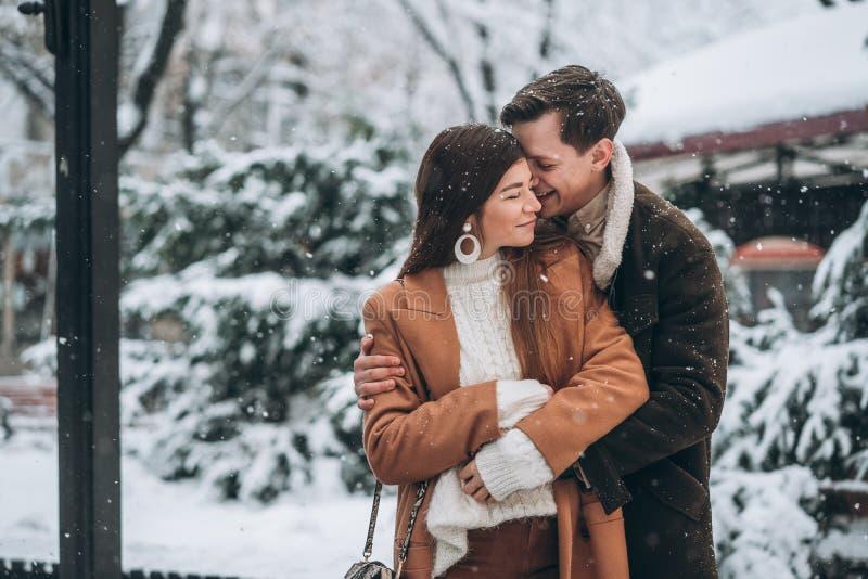 Den unga grabben kramar en härlig flicka i det snöig parkerar arkivfoton