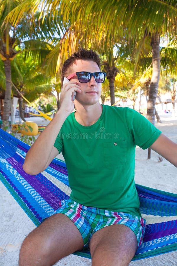 Den unga grabben som talar på telefonen och in kopplar av royaltyfri fotografi