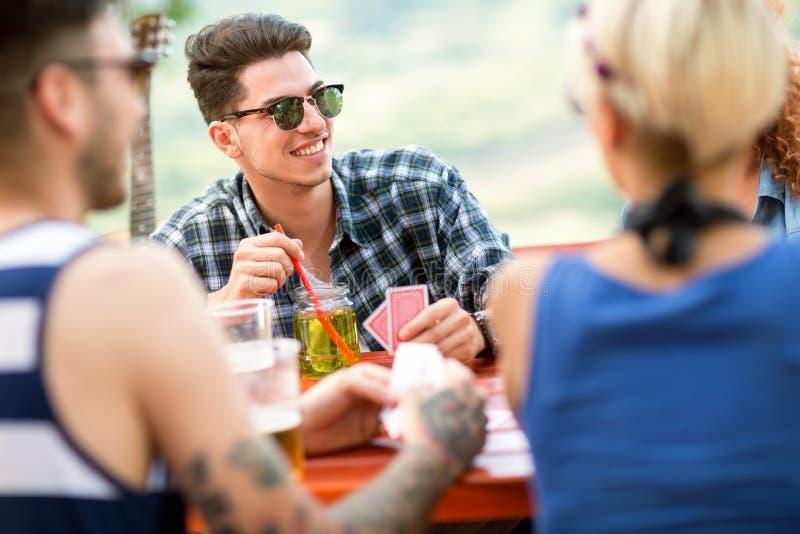 Den unga grabben spelar kort med vänner och drinken arkivfoto