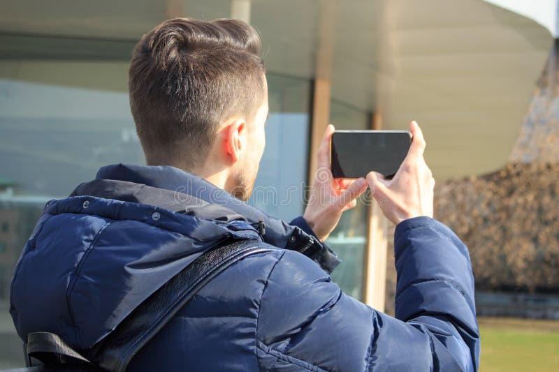 Den unga grabben tar bilder på telefonen i parkerar arkivfoton