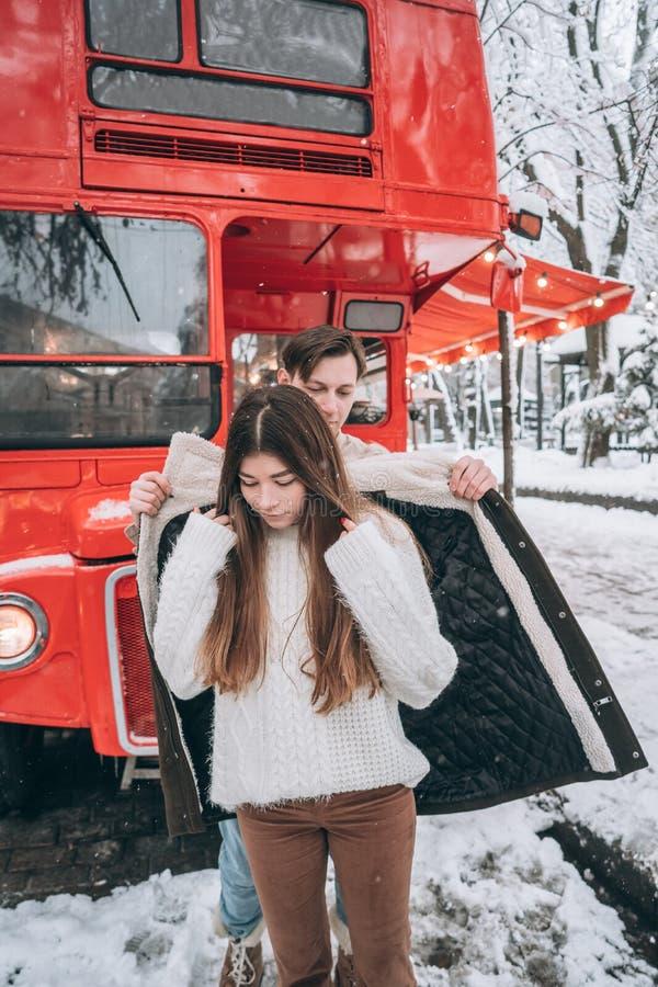 Den unga grabben värme hans härliga flicka med omslaget på en snöig gata arkivfoton