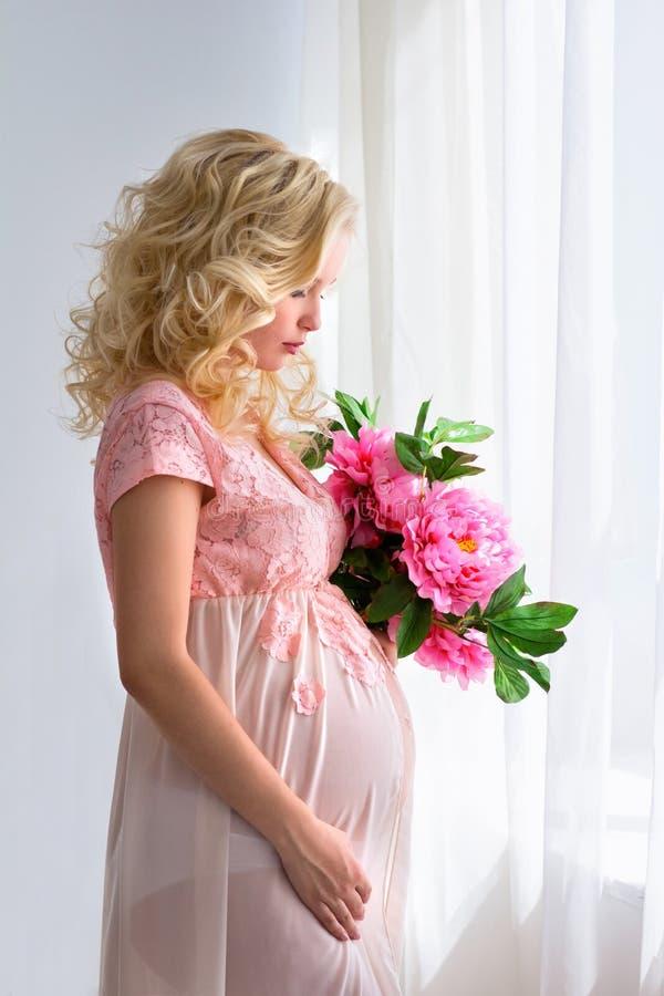 Den unga gravida kvinnan är med blommor vid fönstret royaltyfri fotografi