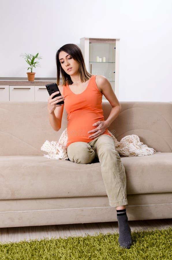 Den unga gravida kvinnan hemma royaltyfria bilder