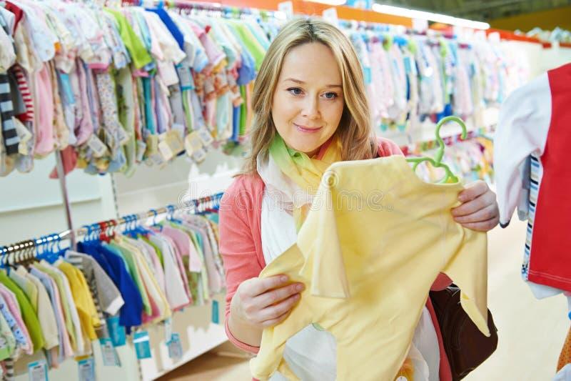 Den unga gravida kvinnan på kläder shoppar royaltyfri foto
