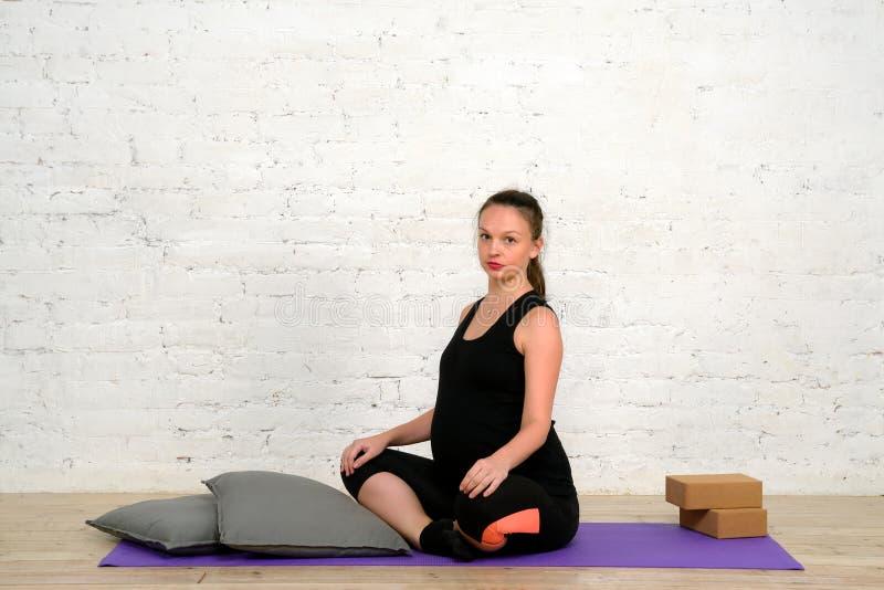 Den unga gravida kvinnan sitter i lotusblommaposition på matt yoga royaltyfria bilder